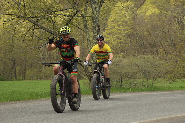 Two cyclists, one with fat bike giving a salute