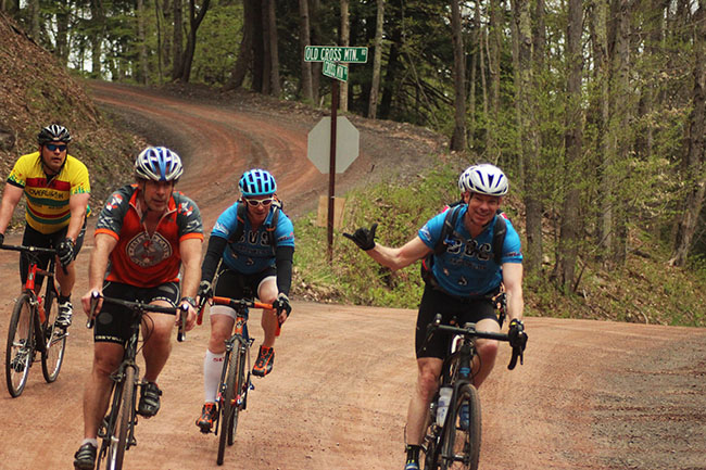 Riders enjoying Cross Mountain Crusher fun on a back road through a wooded area